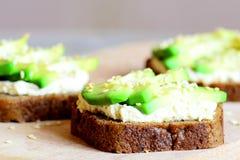 在一个木板的素食鲕梨和hummus三明治 简单和健康单片三明治 健康食物生活方式 免版税图库摄影