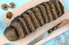 在一个木板的黑麦面包 与向日葵种子,胡说和老刀子的切的面包在桌上 图库摄影