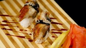 在一个木板设置的寿司卷 转动在黑backround 库存图片