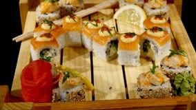 在一个木板设置的寿司卷 转动在黑backround 库存照片