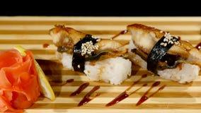 在一个木板设置的寿司卷 转动在黑backround 免版税库存图片