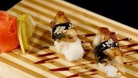 在一个木板设置的寿司卷 转动在黑backround 免版税库存照片