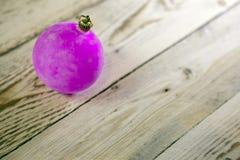 在一个木板,锋利的小深度的桃红色新年` s球 免版税图库摄影