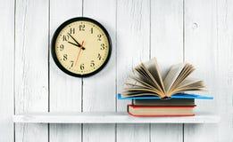 在一个木架子和手表的开放书 免版税库存照片
