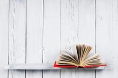 在一个木架子的开放书 免版税库存照片