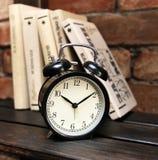 在一个木架子的黑闹钟在书和砖墙的背景中 图库摄影