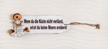 在一个木标志的德国口号与有文本的船锚:如果您 免版税库存照片