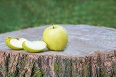 在一个木树桩的一个绿色苹果 库存照片