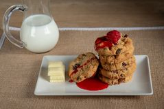 在一个木桌上的巧克力曲奇饼和牛奶罐传统可口食物快餐和葡萄酒桌布草莓和草莓 库存照片
