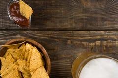 在一个木桌杯子未过滤的啤酒、烤干酪辣味玉米片和辣调味汁上 复制浆糊 库存图片