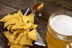 在一个木桌杯子未过滤的啤酒、烤干酪辣味玉米片和辣调味汁上 复制浆糊 库存照片