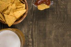 在一个木桌杯子未过滤的啤酒、烤干酪辣味玉米片和辣调味汁上 复制浆糊 免版税库存照片