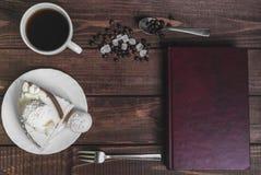 在一个木桌纤巧-有蛋糕的茶碟 免版税库存照片