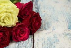 在一个木桌面的背景的五朵玫瑰在葡萄酒st的 免版税库存照片