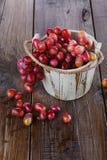 在一个木桶的红葡萄在木背景 免版税库存图片