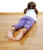 在一个木楼层上的一个小女孩 免版税图库摄影