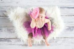 在一个木楼层上的逗人喜爱的女婴 免版税库存图片
