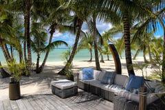 在一个木甲板的藤条椅子在海滩附近 库存照片