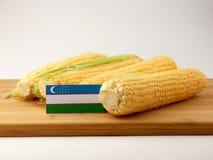在一个木盘区的乌兹别克斯坦旗子用在白色隔绝的玉米 免版税库存图片