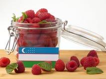 在一个木盘区的乌兹别克斯坦旗子用在a隔绝的莓 库存图片