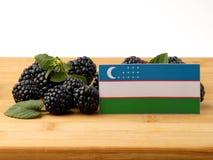 在一个木盘区的乌兹别克斯坦旗子用被隔绝的黑莓  免版税图库摄影