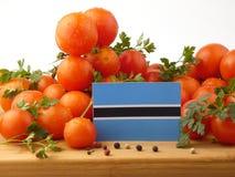 在一个木盘区的博茨瓦纳旗子用在丝毫隔绝的蕃茄 库存照片
