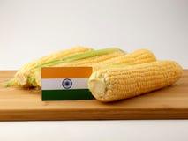在一个木盘区的印地安旗子用在白色后面隔绝的玉米 免版税库存图片