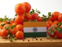 在一个木盘区的印地安旗子用在白色隔绝的蕃茄 库存照片