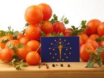 在一个木盘区的印第安纳旗子用在白色隔绝的蕃茄 免版税库存照片