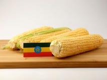 在一个木盘区的埃赛俄比亚的旗子用在白色b隔绝的玉米 库存照片