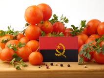 在一个木盘区的安哥拉旗子用在白色隔绝的蕃茄 免版税库存图片