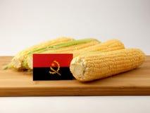 在一个木盘区的安哥拉旗子用在白色bac隔绝的玉米 免版税库存照片