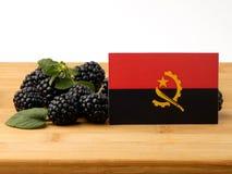 在一个木盘区的安哥拉旗子用在w隔绝的黑莓 免版税图库摄影