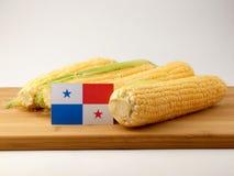 在一个木盘区的巴拿马旗子用在白色隔绝的玉米 库存图片
