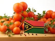 在一个木盘区的瓦努阿图旗子用在白色隔绝的蕃茄 免版税库存照片