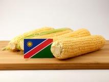 在一个木盘区的纳米比亚旗子用在白色ba隔绝的玉米 库存照片