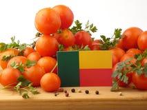 在一个木盘区的贝宁旗子用在白色b隔绝的蕃茄 库存照片