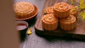 在一个木盘子用茶和花的美丽的月饼在黑板岩背景 中国传统中秋 影视素材
