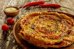 在一个木盘子的自创圆的菜饼服务用新鲜的西红柿、辣椒和芝麻籽 免版税图库摄影