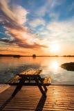 在一个木码头的长凳在日落 免版税库存照片