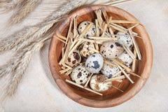 在一个木碗和麦子耳朵的鹌鹑蛋在亚麻布 免版税库存照片