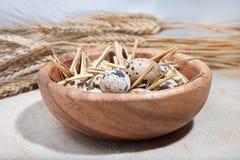 在一个木碗和麦子耳朵的鹌鹑蛋 免版税图库摄影