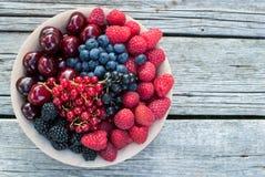 在一个木碗的各种各样的果子在葡萄酒木背景 库存照片