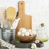 在一个木碗的新鲜的蘑菇在一个厨房白色砖墙的背景有切板的,厨房器物 库存图片