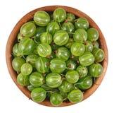 在一个木碗的新鲜的绿色鹅莓在白色 库存图片