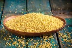 在一个木碗的有机小米种子 免版税图库摄影