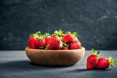 在一个木碗的有机新鲜的成熟草莓在黑暗的背景 健康果子和莓果, vegaterian食物 库存照片