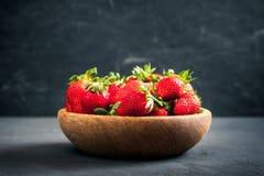 在一个木碗的有机新鲜的成熟草莓在黑暗的背景 健康果子和莓果, vegaterian食物 图库摄影