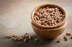 在一个木碗的未加工的有机鸡豆,健康素食主义者素食食品成分 库存图片