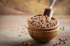 在一个木碗的未加工的有机鸡豆,健康素食主义者素食食品成分 免版税图库摄影